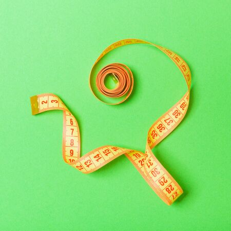 Top view of curled measuring tape as a sewing accessory on green background. Tailor concept with copy space.