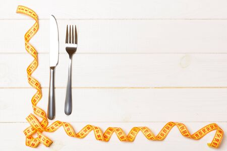Top view composition of fork and knife with curled measuring tape on wooden background with empty space for your ideas. Overweight and overeating concept. 스톡 콘텐츠