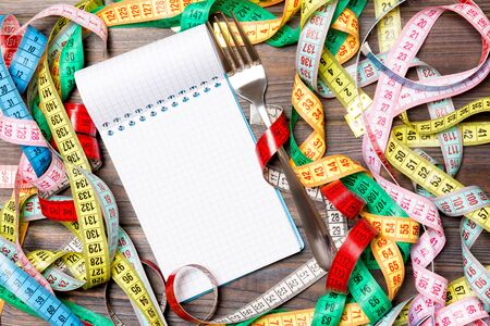 Group of colorful measure tapes, open notebook and fork on wooden background with empty space for your idea. Top view of healthy lifestyle concept.
