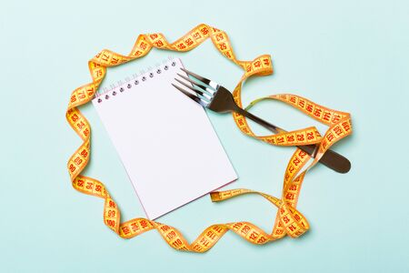 Group of colorful measure tapes, open notebook and fork on blue background with empty space for your idea. Top view of healthy lifestyle concept.