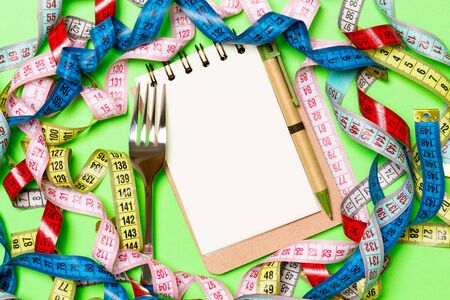 Group of colorful measure tapes, pen, open notebook and fork on green background with empty space for your idea. Top view of healthy lifestyle concept.