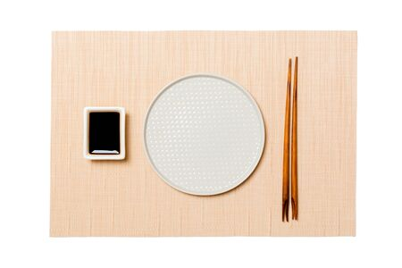 Empty round white plate with chopsticks for sushi and soy sauce on brown sushi mat background. Top view with copy space for you design. Banque d'images