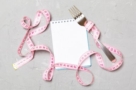 Pink measure tape, open notebook and fork on cement background with empty space for your idea. Top view of healthy lifestyle concept. Stockfoto