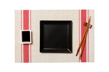 Empty black square plate with chopsticks for sushi and soy sauce on sushi mat background. Top view with copy space for you design.