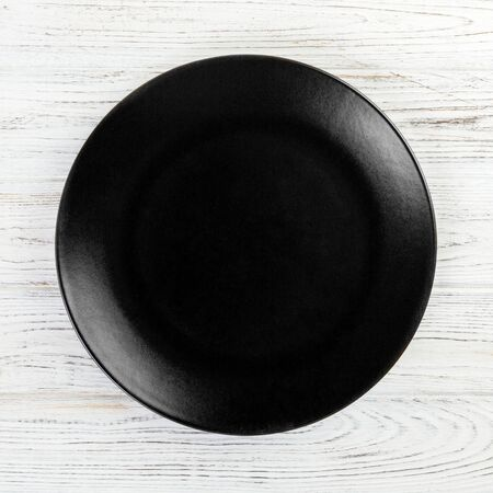 Black round plate on wooden background, top view, copy space. 스톡 콘텐츠