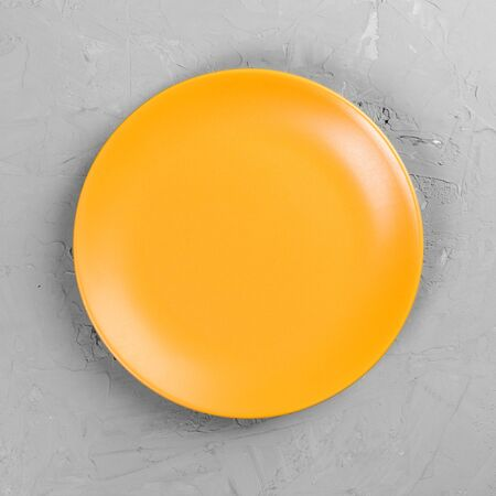 Yellow Round Plate on grey cement table background. Top view, template for your design. 스톡 콘텐츠