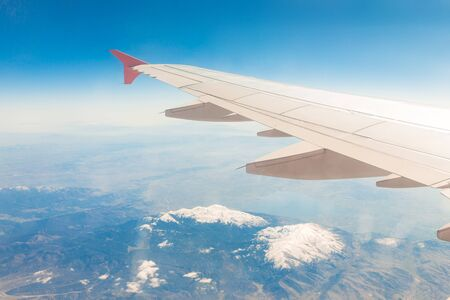 Aircraft wing on the clouds, flies on the mountains background. Фото со стока