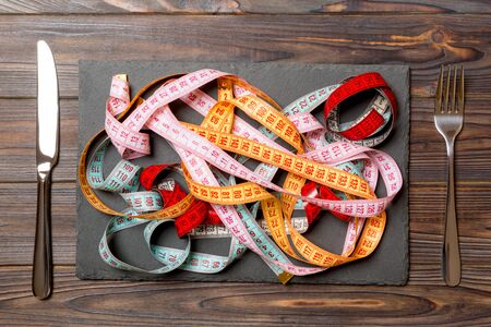Top view of heap of colorful measuring tapes in plate on wooden background. Diet concept with copy space.