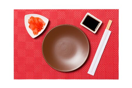 Empty round brown plate with chopsticks for sushi and soy sauce, ginger on red mat sushi background. Top view with copy space for you design.