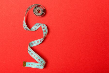 Tangled measuring tape with space for your idea. Sewing and tailor concept on red background. Stok Fotoğraf