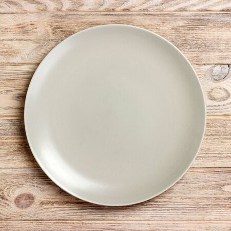Top view with empty for you design. Empty white plate on wooden background. 스톡 콘텐츠