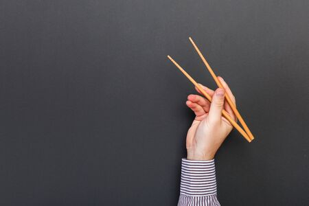 Creative image of wooden chopsticks in male hands on black background. Japanese and chinese food with copy space. Banque d'images