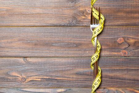 Top view of wrapped fork in tape measure on wooden background. Healthy eating and diet concept. Stock fotó