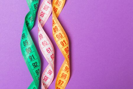 Close up of colorful measure tapes on purple background. Perfect female figure measurements concept. Stockfoto