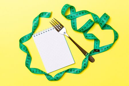 Top view of weight loss concept on yellow background. Mix of green centimeter tape, note pad and fork with space for your design. Zdjęcie Seryjne