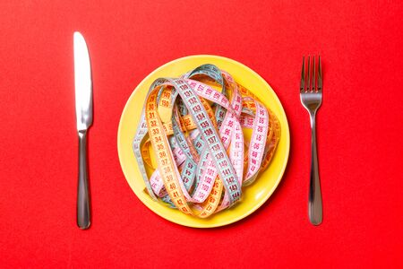 Top view of heap of colorful measuring tapes in plate on red background. Diet concept with copy space.