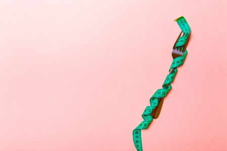Fork wrapped in measuring tape on pink background with copy space. Top view of proper diet concept.