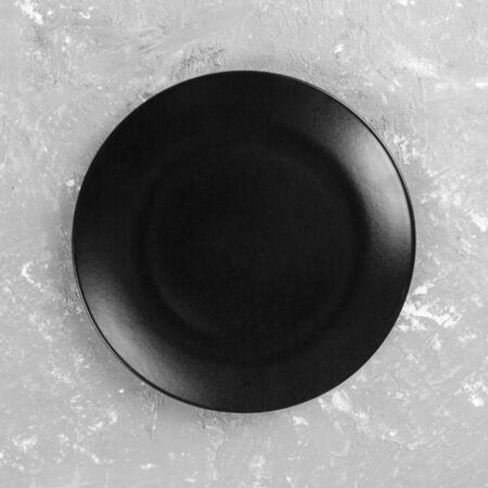 Black round plate on gray cement background, top view, copy space.