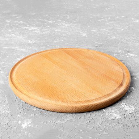 Lege ronde houten plaat op getextureerde tafel. Houten plaat voor eten of groente serveren aan klanten. Stockfoto