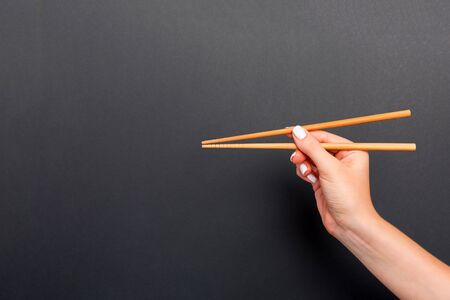 Wooden chopsticks in female hand on black background with empty space for your idea. Tasty food concept. Stock Photo