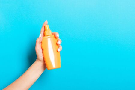 Female hand holding spray cream bottle of lotion isolated. Girl give cosmetic products on blue background.