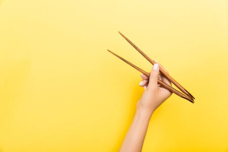 Female hand with chopsticks on yellow background. Traditional asian food with emty space for your design.