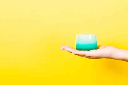 Female hand holding cream bottle of lotion isolated. Girl give jar cosmetic products on yellow background. Reklamní fotografie - 129777340