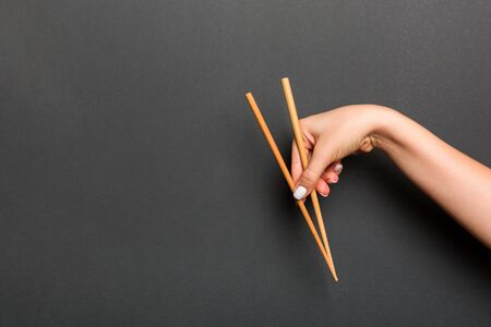 Wooden chopsticks holded with female hands on black background. Ready for eating concepts with empty space. Stock Photo