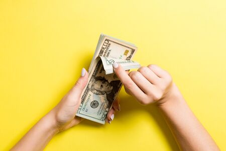 Top view of female hands counting money. Various dollar banknotes on colorful background. Salary concept. Bribe concept.