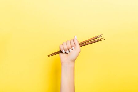 Cropped image of female hand holding chopsticks in fist on yellow background. Asian food concept with copy space.