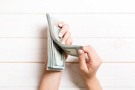 Top view of a businesswoman's hands counting one hundred dollar banknotes on wooden background. Success and wealth concept. Banque d'images