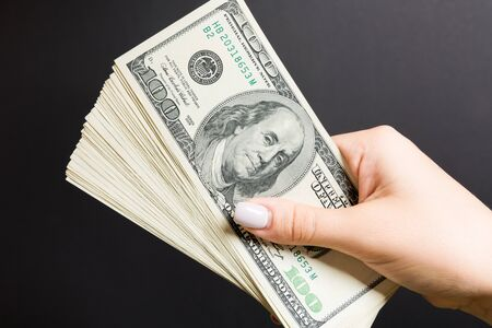 Top view of female hand holding a fan of one hundred dollars on colorful background. Loan concept. Prosperity concept.