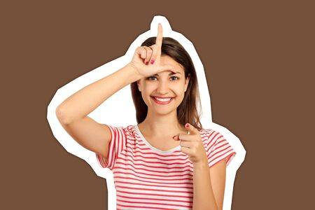 a happy woman gives a sign of the loser on his forehead, looking at you and pointing his finger at the camera. emotional girl Magazine collage style with trendy color background. Standard-Bild