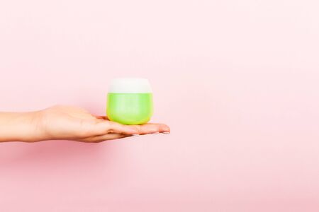 Female hand holding cream bottle of lotion isolated. Girl give jar cosmetic products on pink background.