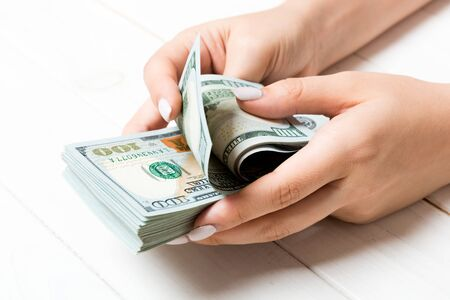 Perspective view of female hands counting money. One hundred dollar banknotes on wooden background. Salary concept. Bribe concept. Imagens
