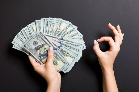 Top view of one hundred dollar bills in one hand and showing okay gesture with another hand on colorful background. Prosperity and fortune concept.