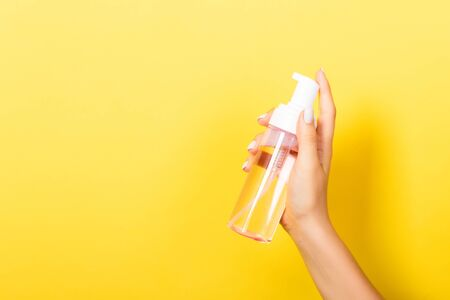 Female hand holding spray cream bottle of lotion isolated. Girl give cosmetic products on yellow background.