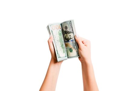 Top view of a bundle of money in female hands. Image of counting dollars on white isolated background. Tax concept.