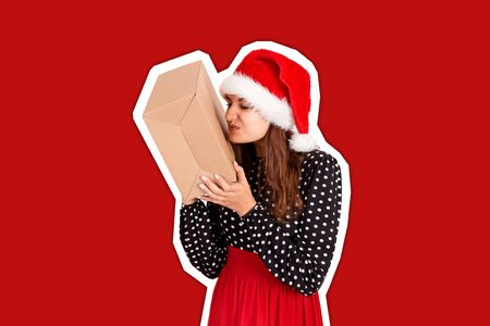 disappointed girl in christmas hat holding a big gift in her hand. Magazine collage style with trendy color background. holidays concept. Banque d'images