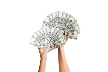 Top view of female hands giving a fan of dollar bills on isolated background. Profit and luxury concept.