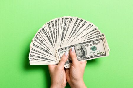 Fan of one hundred dollar bills in female hand on colorful background. Investment concept. Banco de Imagens
