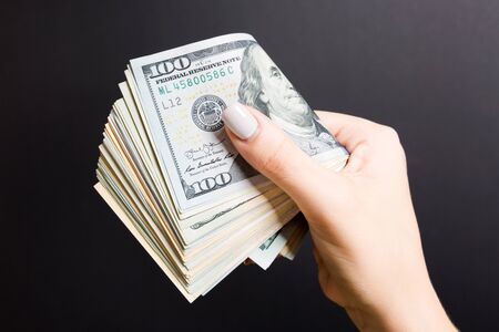 Female hand holding tightly a bundle of money. Top view of one hundred and different dollars on colorful background. Investment concept .