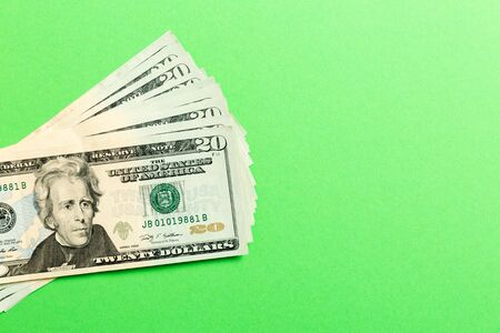 Stack of 20 dollar banknotes on colorful background. Top view of financial concept with empty space for your design.