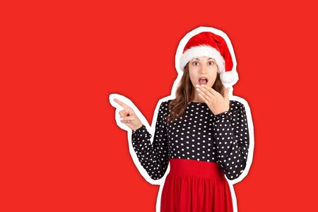 Girl in dress surprise showing product. emotional girl in santa claus christmas hat Magazine collage style with trendy color background. holiday concept.