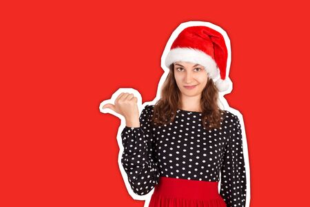 portrait of woman in dress pointing left with thumb and upset. emotional girl in santa claus christmas hat Magazine collage style with trendy color background. holiday concept. Stok Fotoğraf