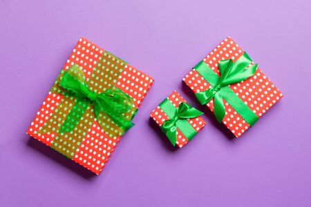 Gift box with green bow in hands for Christmas or New Year day on purple background, top view.