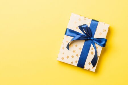 Top view present box with blue bow on yellow background with copy space.