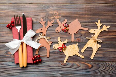 Top view of holiday objects on wooden background. Utensils tied up with ribbon on napkin. Close up of christmas decorations and reindeer. New year dinner concept.