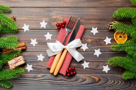 Top view of utensils on festive napkin on wooden background. Christmas decorations with dried fruits and cinnamon. Close up of New year dinner concept.