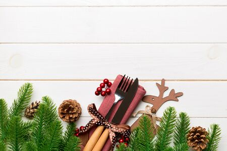 Top view of flatware tied up with ribbon on napkin on wooden background. Christmas decorations and reindeer with empty space for your design. New Year holiday concept.